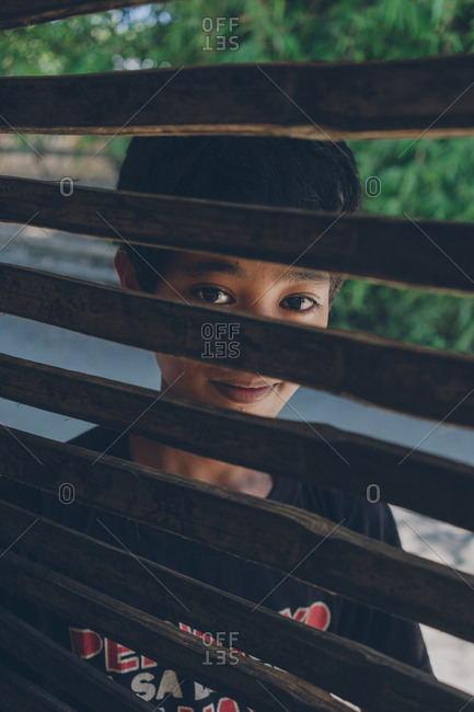 PHILIPPINES, APRIL 16, 2018: Smiling asian kid standing outdoors and looking through lattice at camera