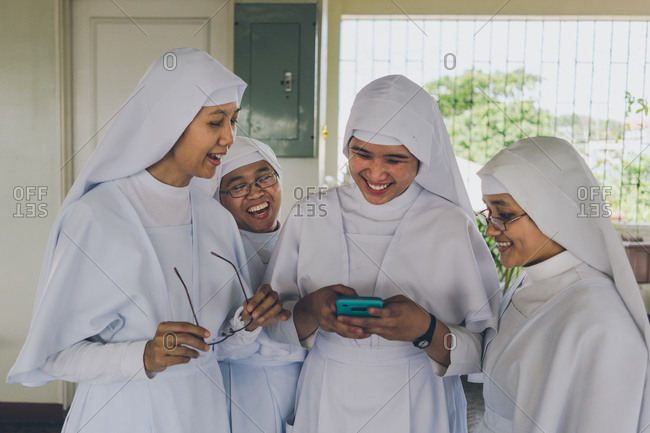 PHILIPPINES, APRIL 16, 2018: Group of cheerful nuns in white gowns using smartphone and having fun in church living