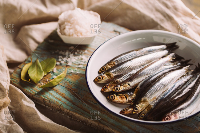 Fresh anchovies in a plate with a rustic background