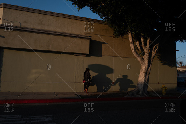 Shadowy people walking on sidewalk next to building