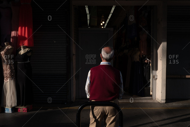 Back of man standing still looking into dark hallway