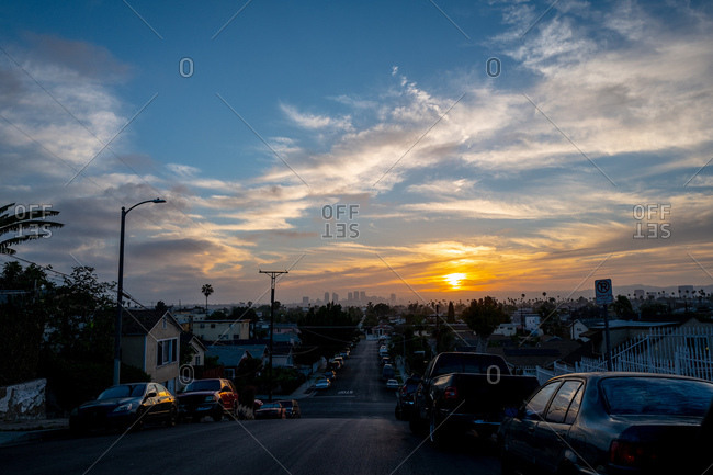 View of sunset over city from deserted neighborhood street