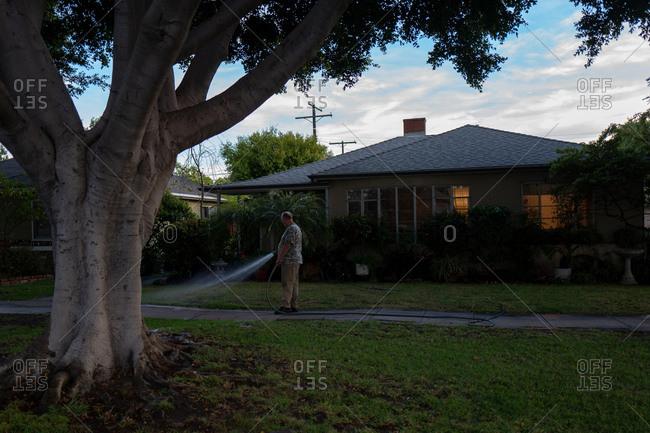 Culver City, California - May 5, 2018: Man watering lawn at dusk