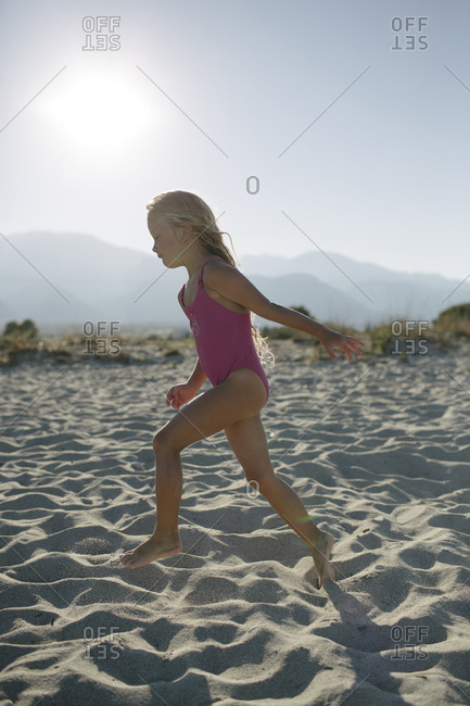 Young girl in bathing suit running on beach