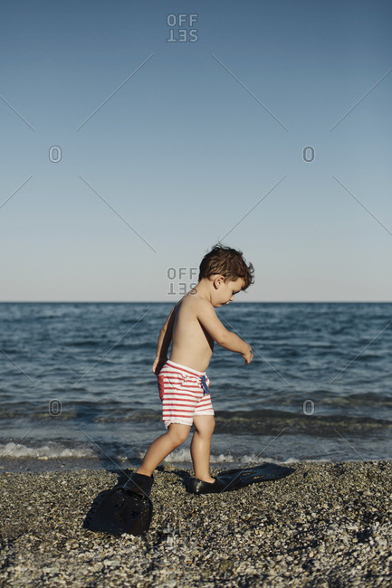 Toddler boy walking in rubber fins on beach
