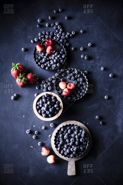 Top view of various berries in vintage baking supplies
