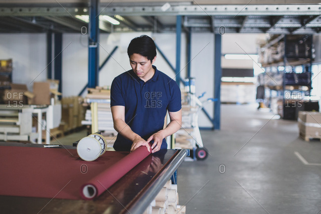 Male cutting fabric in a manufacturing warehouse