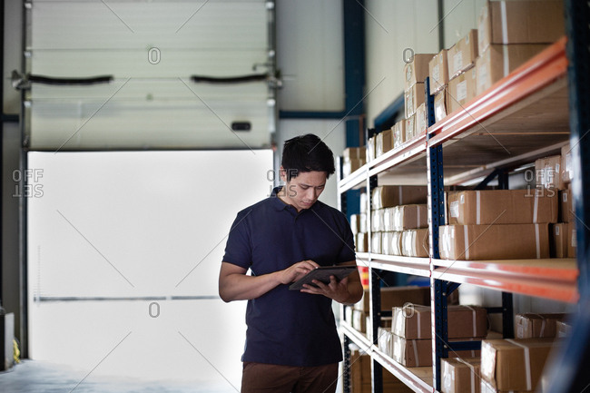 Male working in distribution warehouse with digital tablet