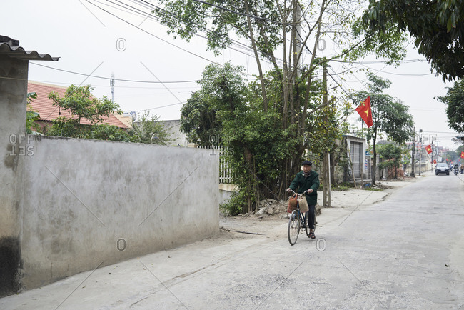 Ninh Binh, Vietnam - February 9, 2018: Senior man riding a bicycle with bags hanging on the handlebar