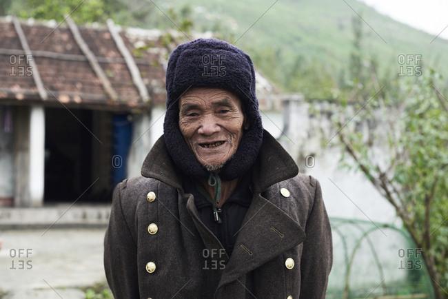 Quang Dong, Vietnam - February 2, 2018: Centenarian elderly vietnamese man looking at camera cheerful wearing coat and bearskin.