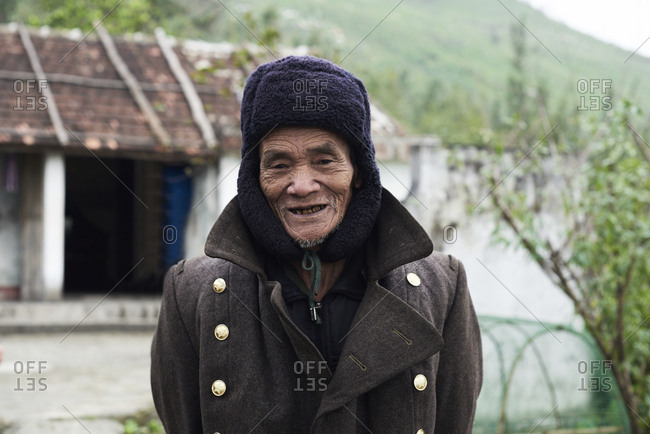 Quang Dong, Vietnam - February 2, 2018: Centenarian elderly vietnamese man looking at camera cheerful wearing coat and bearskin.