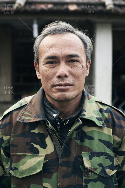 Quang Dong, Vietnam - February 2, 2018: Grey-haired senior man in military uniform looking at camera serious outside his house.