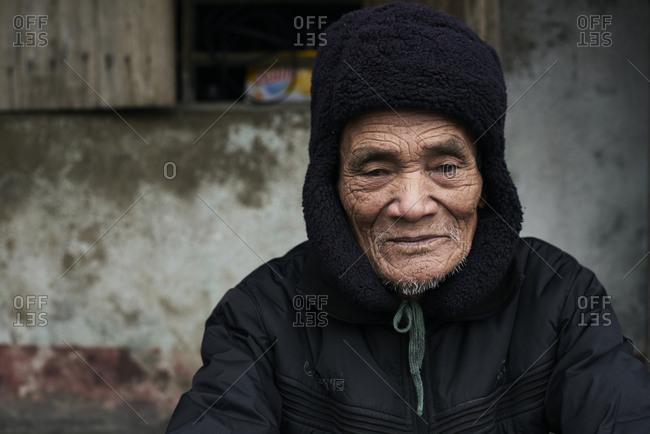 Quang Dong, Vietnam - February 2, 2018: Centenarian elderly vietnamese man looking at camera serious wearing coat and bearskin.