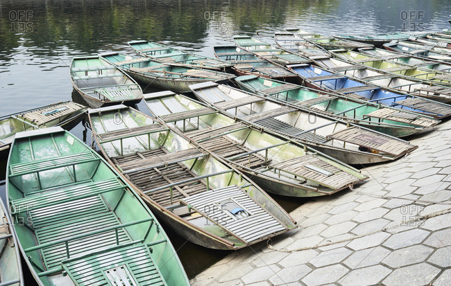 Bunch of colorful boats moored in harbor ready for tourists at Tam Coc, Ninh Binh, Vietnam.