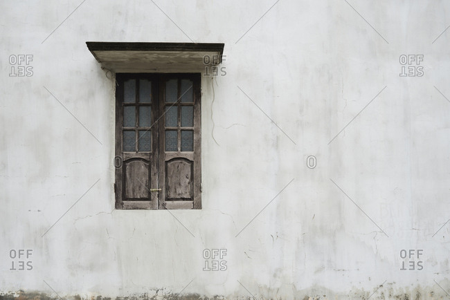 Minimal shot of classic window built in wood against grey wall.