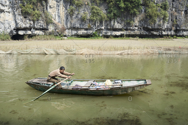 Ninh Binh, Vietnam - February 9, 2018: Strong vietnamese male padding boat across river in Tam Coc, Vietnam.