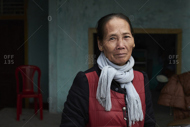 Quang Dong, Vietnam - February 1, 2018: Portrait of elderly vietnamese woman wearing scarf and coat outside her home place looking at camera.