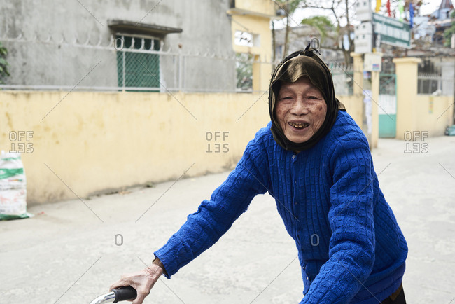 Ninh Binh, Vietnam - February 9, 2018: Elderly injured woman walking with rollator on the street and looking cheerful at camera.