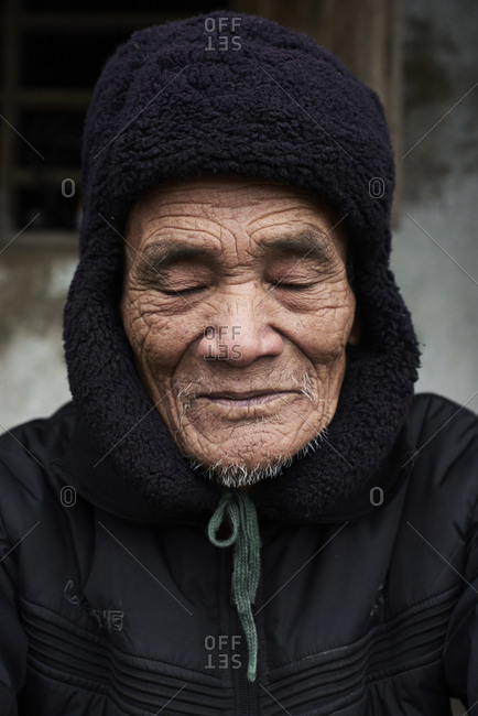 Quang Dong, Vietnam - February 2, 2018: Centenarian elderly vietnamese man meditating with eyes closed wearing coat and bearskin.