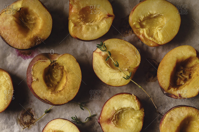 Grilled peaches and nectarines halved on baking paper sheet with thyme