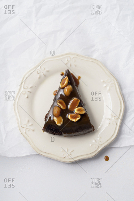 A piece of brownie cake with salted caramel and roasted peanuts
