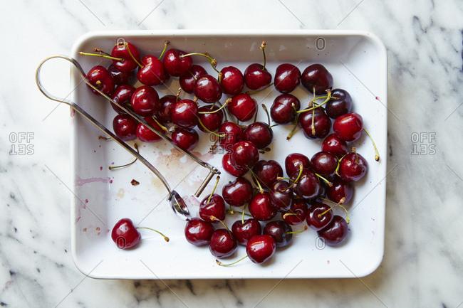 Fresh cherries on white plate cherry pitter