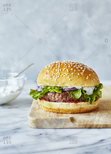 Lamb burger in brioche bun with mint yoghurt, served on a wooden board