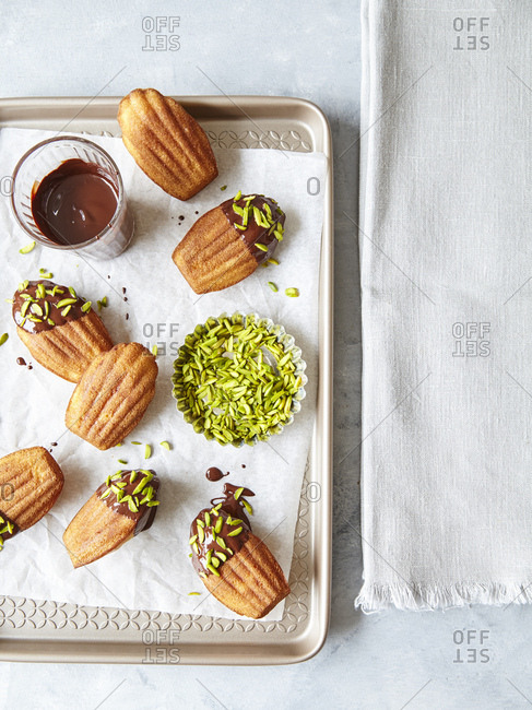 Madeleines dipped in chocolate and pistachios on baking tray