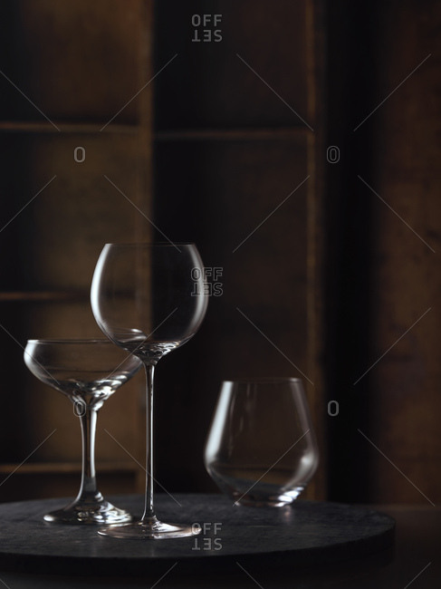 A variety of wine glasses in a warm rustic setting on a dark granite surface.