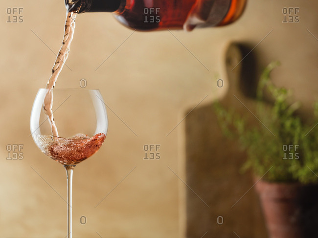 Rose being poured into delicate wine glass in a warm, tuscan kitchen setting.