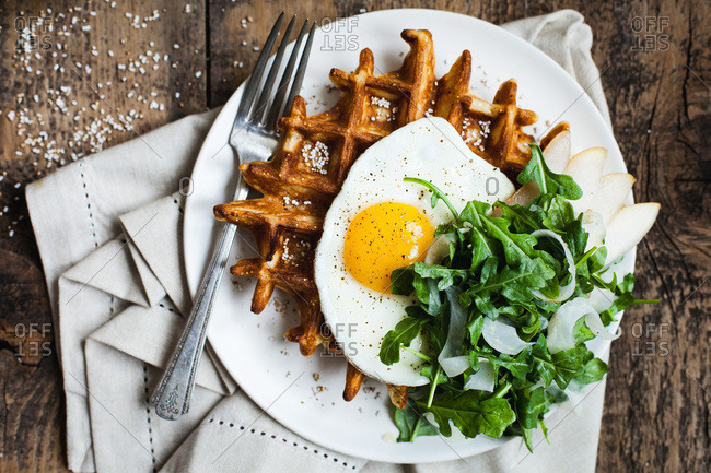 Waffles with egg and greens on plate