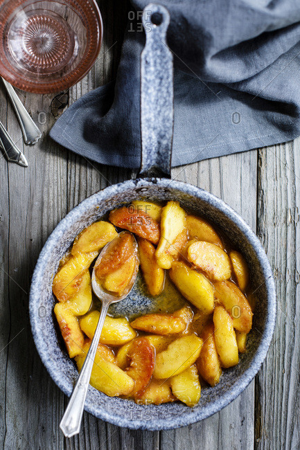 Cooked peaches in a skillet on a wooden background