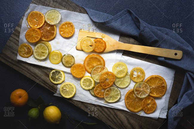 Slices of candied citrus fruit cooling on baking paper.