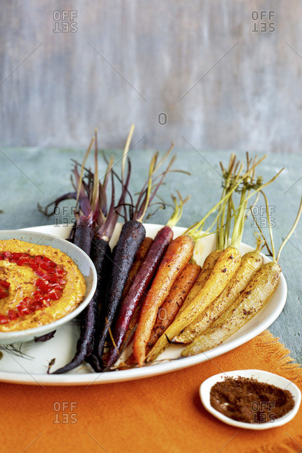 Sumac Roasted Carrots�with Roasted Red Pepper Harissa Pesto. Photographed on a green background.