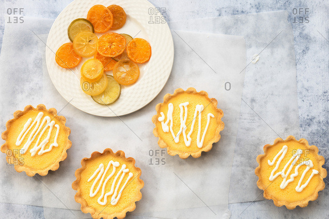 Small lemon tarts with a plate of candied orange, lime and lemon slices.