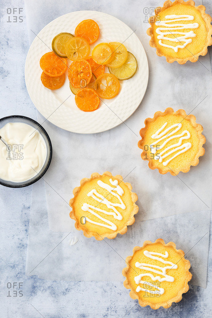 Four lemon tarts with a bowl of yoghurt and a plate of candied lemon, lime and orange slices.