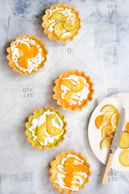 Five lemon, lime and orange tarts with a plate of candied citrus fruit slices viewed from above.