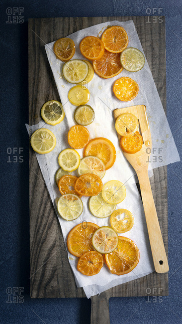 Slices of candied orange, lemon and lime in syrup cooling on baking paper with a wooden spatula.