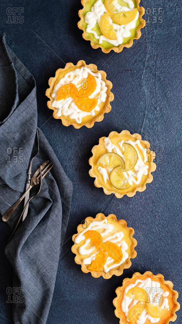 Lemon, lime and orange tarts decorated with yoghurt and candied fruit slices on a blue textured background.