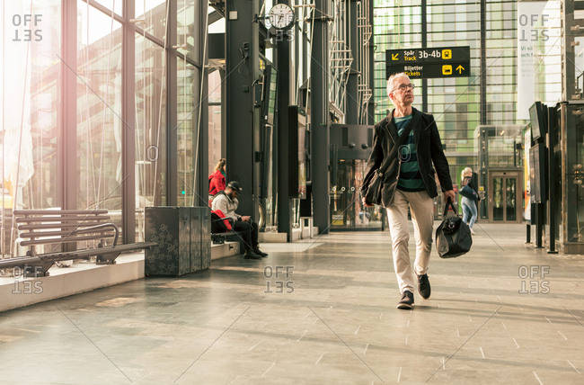 Full length of senior male commuter walking with luggage at railroad station