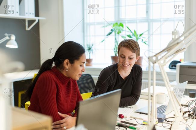 Smiling multi-ethnic female professionals working at illuminated desk in creative office