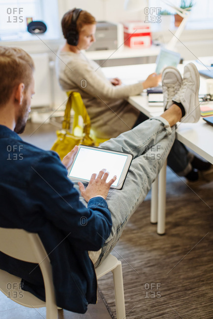 Full length of young businessman using digital tablet while sitting by female colleague working at desk in office