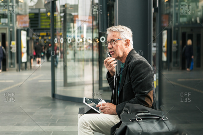 Senior male commuter talking through in-ear headphones while sitting by bags at railroad station
