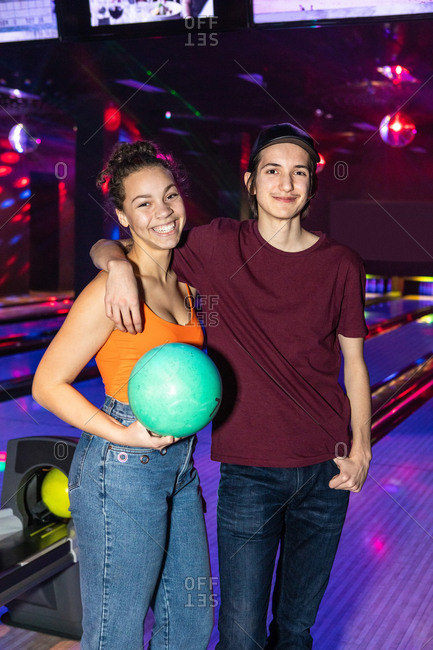 Portrait of smiling teenage friends standing with ball at bowling alley