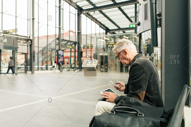 Senior male commuter sitting with technologies and bags at railroad station