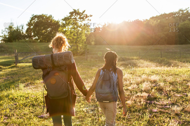 Rear view of girl and woman with backpacks holding hands while hiking on grass at public park during sunset