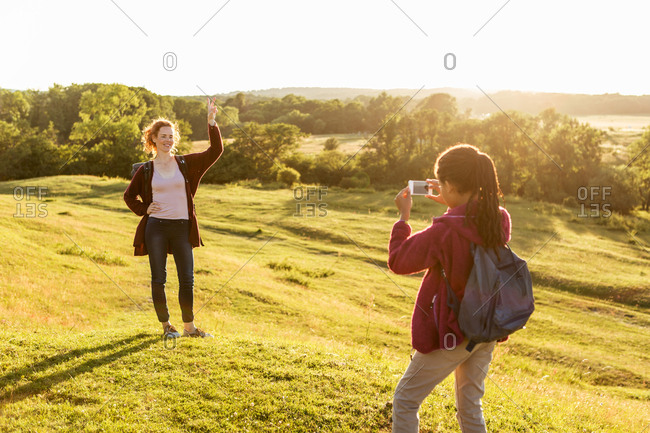 Rear view of girl photographing happy mother showing peace sign on field against clear sky during sunset