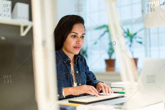 Confident businesswoman using laptop while sitting at desk in creative office
