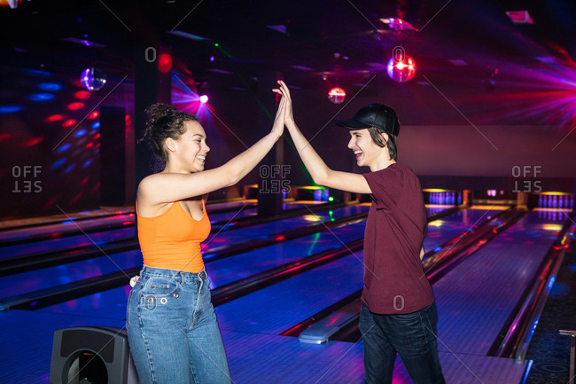 Cheerful friends giving high-five on illuminated parquet floor at bowling alley