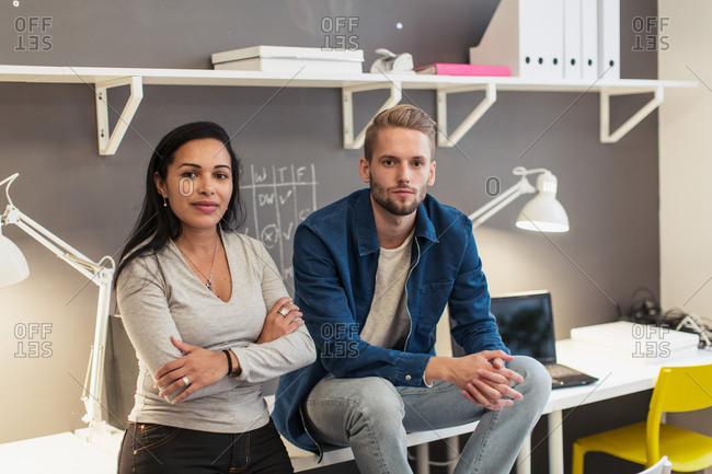Portrait of confident business colleagues sitting on desk against wall at creative office